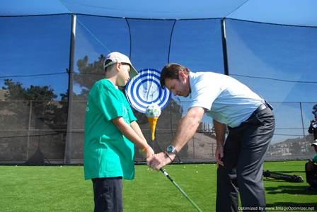 Man teaching kid to drive a golf ball from an artificial turf driving range
