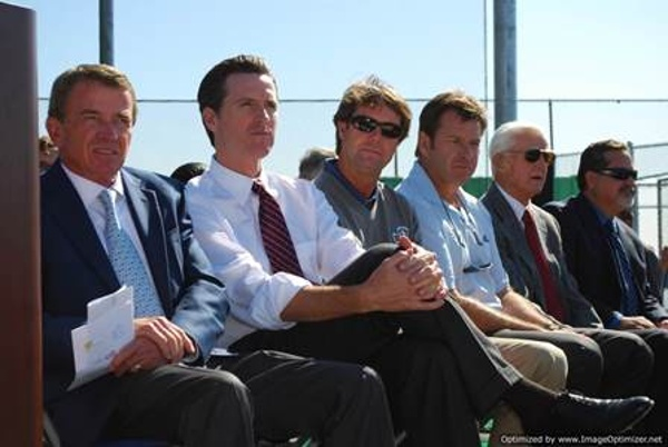 6 Guys sitting down watching the activities on the artificial turf driving range
