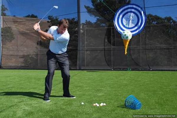 Man driving golf ball from tee on artificial turf