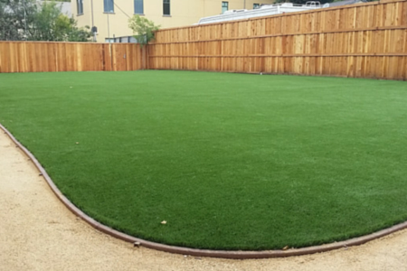 artificial lawn in a backyard with a fence