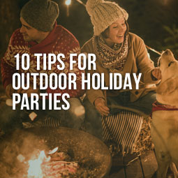 a couple with their dog by the firepit having a great outdoor holiday party